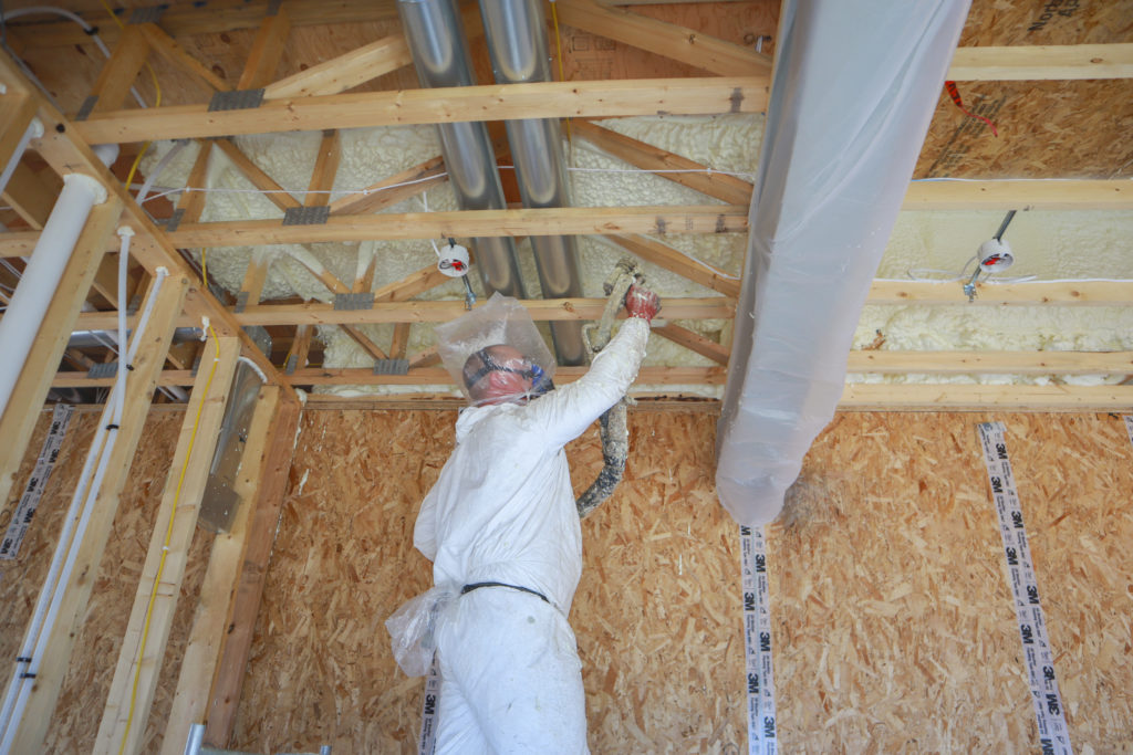 Man in protective suit spraying a ceiling with insulating foam